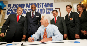Alonzo Mourning stands with Governor Charlie Crist as he signs the Alonzo Mourning Access to Care Act.